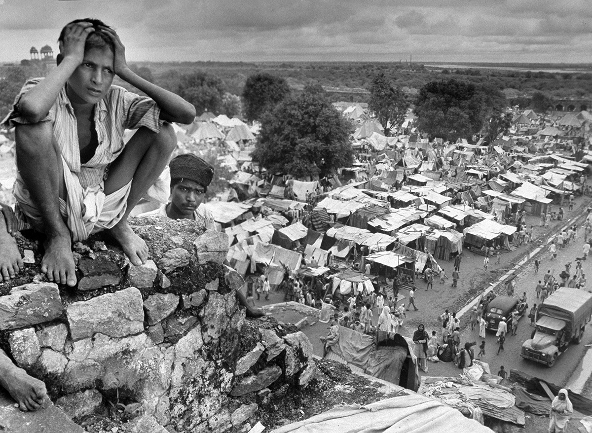 Migration India, October 1947: Boy sitting on rock ledge above refugee camp.